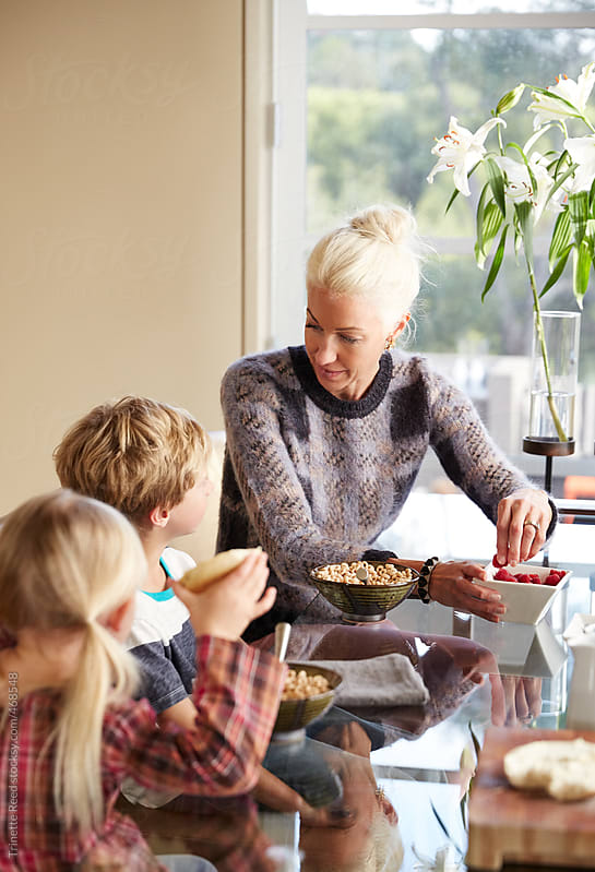 Mom having breakfast with her kids in the morning by Trinette Reed for Stocksy United