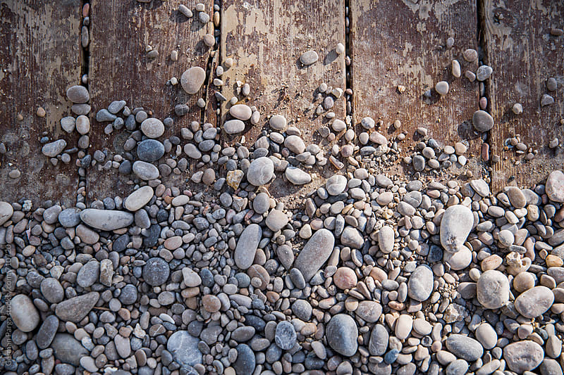 A patter of mixed beach stones laying over a wooden background by German Parga for Stocksy United