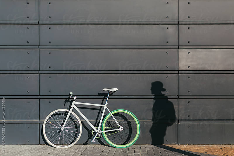 Fixie Bicycle Leaning on a Metallic Wall Besides a Man Shadow by VICTOR TORRES for Stocksy United