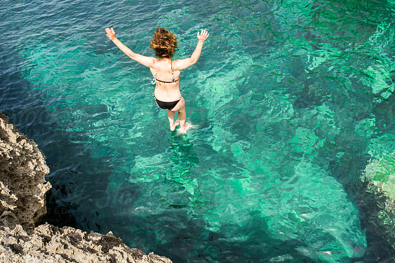 Woman jumping into the ocean on vacation by Aila Images for Stocksy United