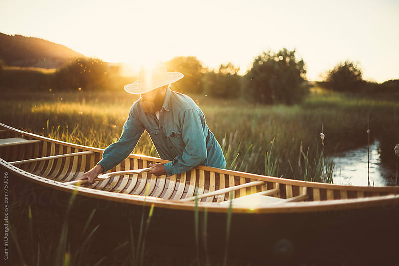 Man and Canoe at Sunset by Camrin Dengel for Stocksy United