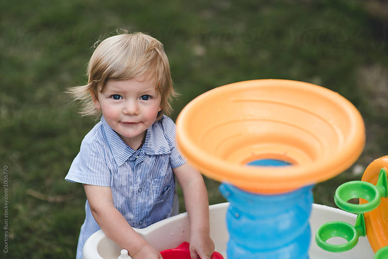 sweet boy playing with water on a hot day  by Courtney Rust for Stocksy United