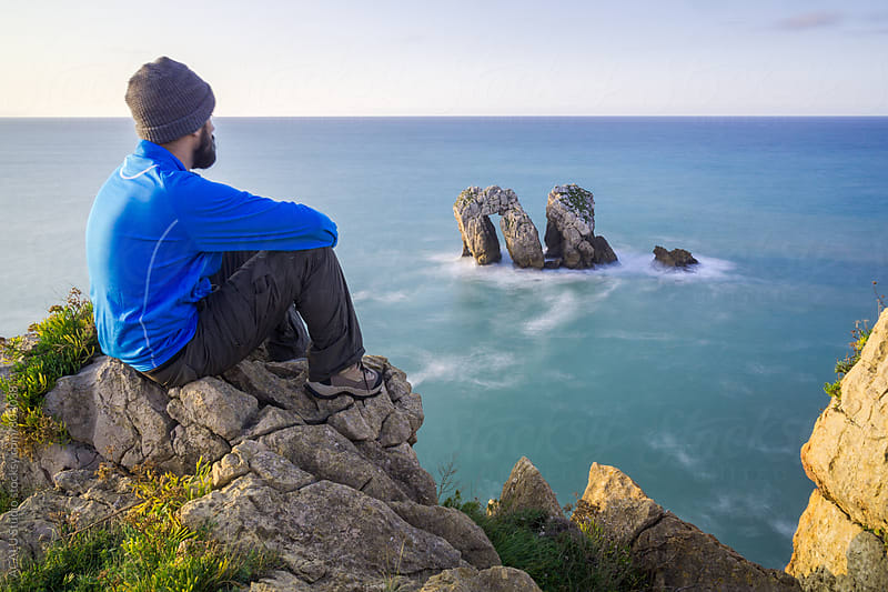 Man contemplating the seascape on the edge of a cliff by ACALU Studio for Stocksy United