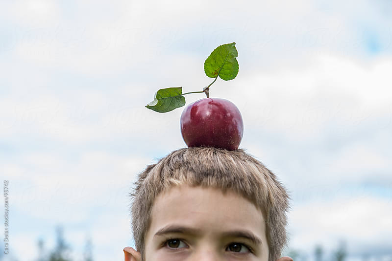 Boy has an apple on top of his head by Cara Dolan for Stocksy United