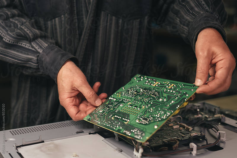 Technician holding a circuit board  by RG&B Images for Stocksy United