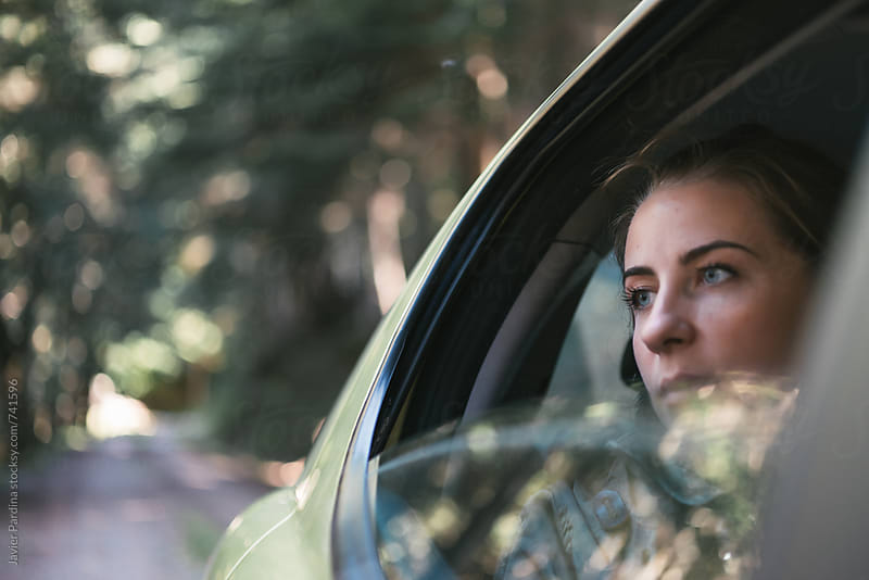 woman looking in the forest from car by Javier Pardina for Stocksy United