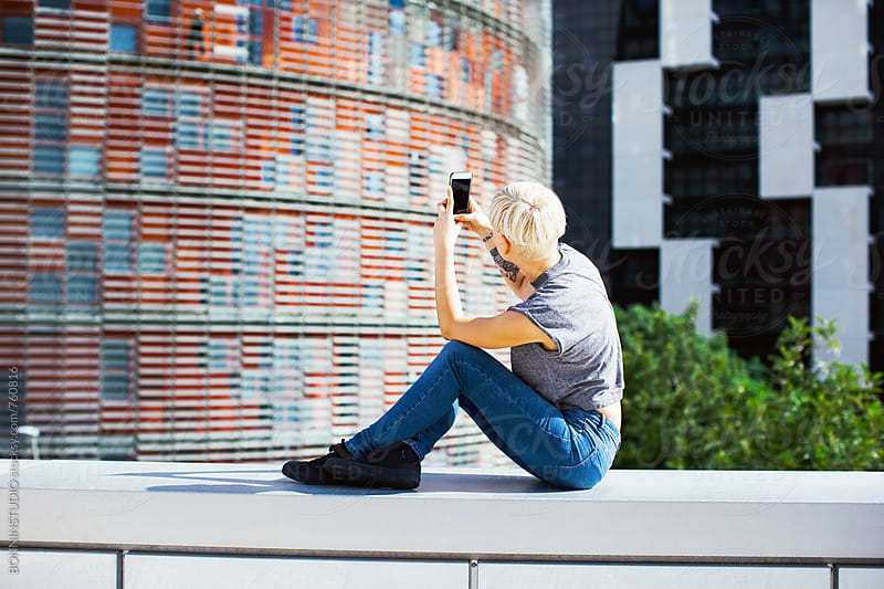 Side view of a woman taking a photo of the city. by BONNINSTUDIO for Stocksy United