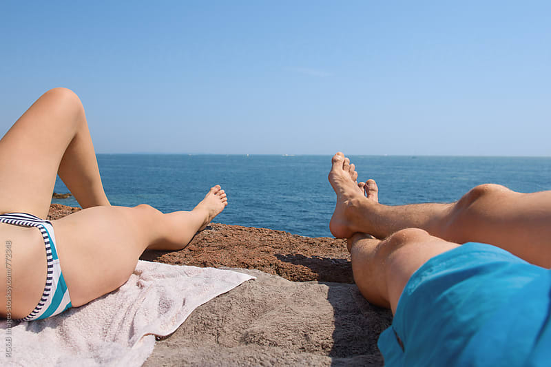 Couple sunbathing on a rock near the sea by RG&B Images for Stocksy United