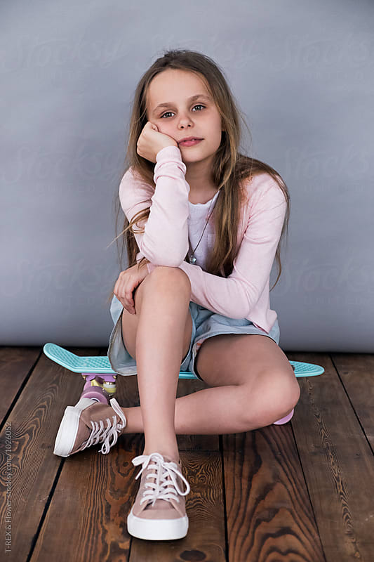 Portrait of girl sitting on skate and looking at camera by Danil Nevsky for Stocksy United