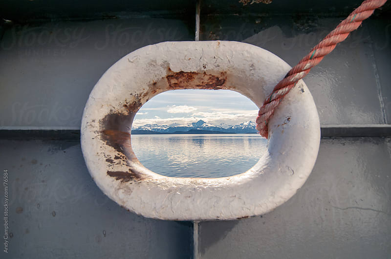 A view of the ocean and Alaskan mountains through a ship's porthole by Andy Campbell for Stocksy United