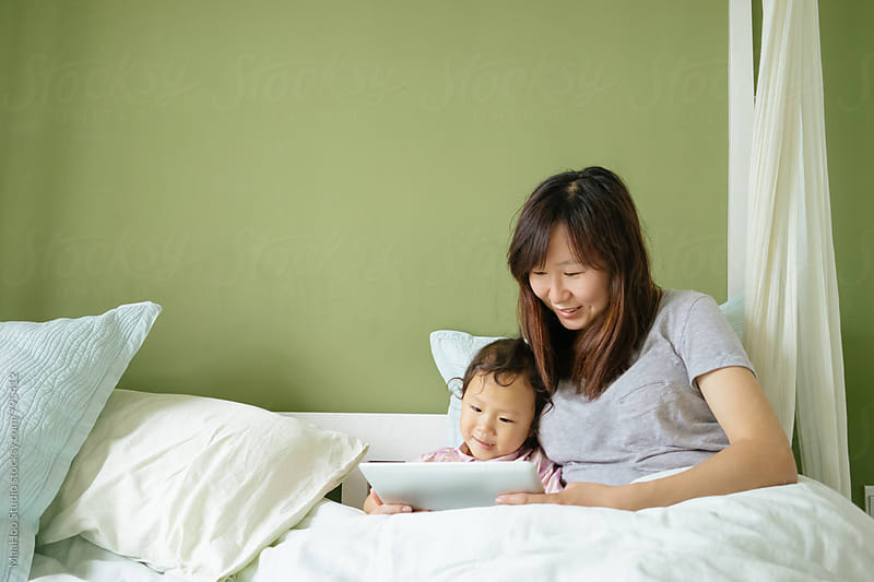 Toddler girl using digital PC with her mother on bed by MaaHoo Studio for Stocksy United