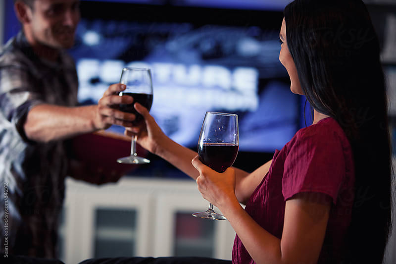 Television: Girlfriend Hands Wine To Man Before Movie Starts by Sean Locke for Stocksy United