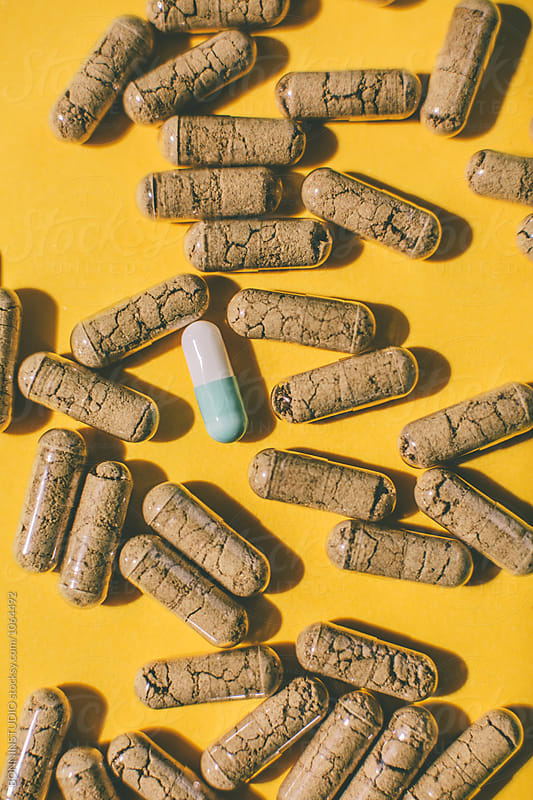 Bicolor pill around vitamin capsules on yellow background.  by BONNINSTUDIO for Stocksy United