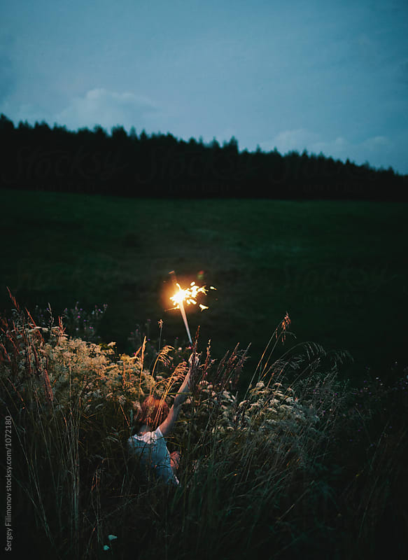 girl holding a burning sparkler by Sergey Filimonov for Stocksy United