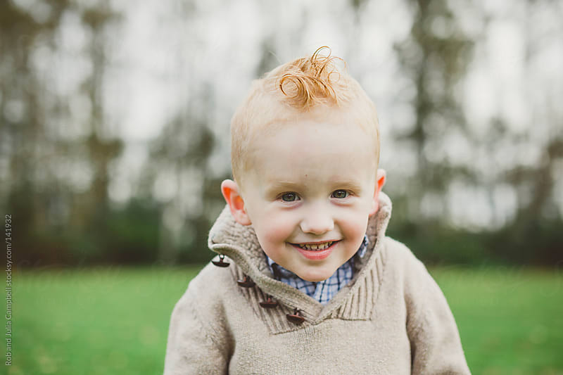 Portrait of a cute young toddler smiling in a field by Rob and Julia Campbell for Stocksy United