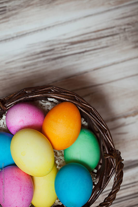 Easter: Basket Of Colorful Eggs On Wooden Background by Sean Locke for Stocksy United