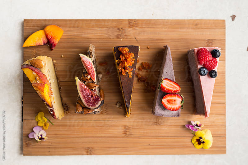 raw vegan cake slices on a timber board by Gillian Vann for Stocksy United
