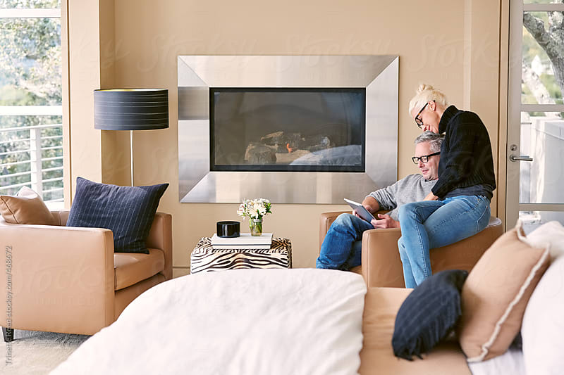 Couple relaxing in luxury bedroom at home with technology  by Trinette Reed for Stocksy United