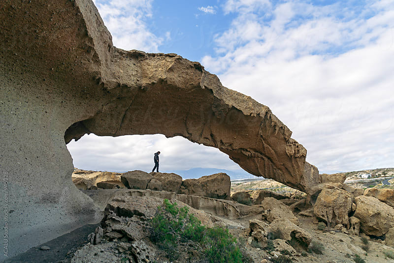 Man walking under a natural arch by ACALU Studio for Stocksy United