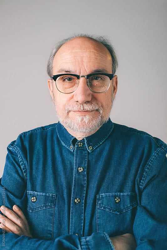Portrait of a serious mature man wearing modern glasses and denim shirt. by BONNINSTUDIO for Stocksy United