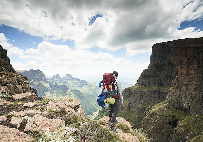 A male hiker with his backpack standing at a mountain cliff edge over a mountainous green valley with clouds. by Jacques van Zyl for Stocksy United