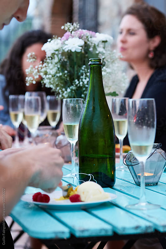 View of friends eating ice cream with glaases of champagne on table