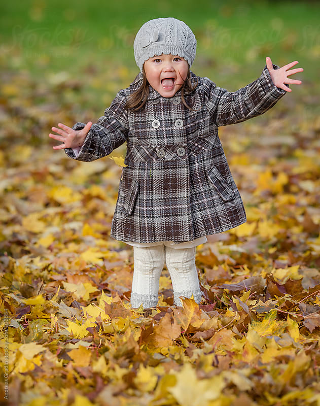 young girl playing with autumn leaves by Andreas Gradin for Stocksy United