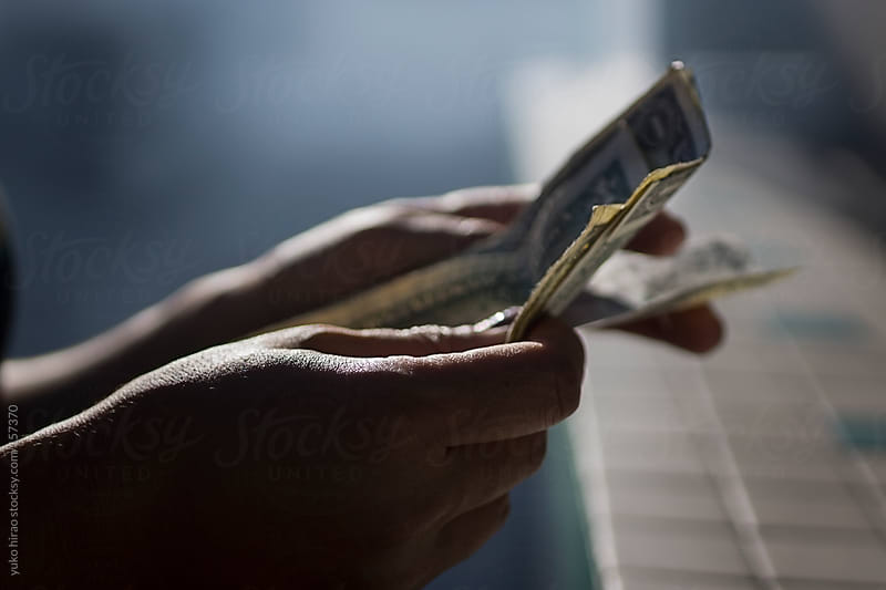 Seller's hands, counting money at a bazaar in smoke by yuko hirao for Stocksy United
