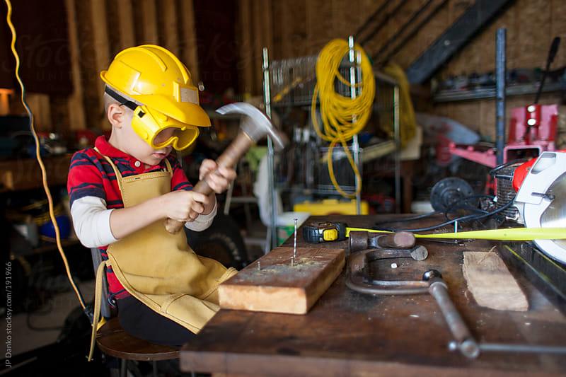 Little Boy Working In Garage With Hammer by JP Danko for Stocksy United