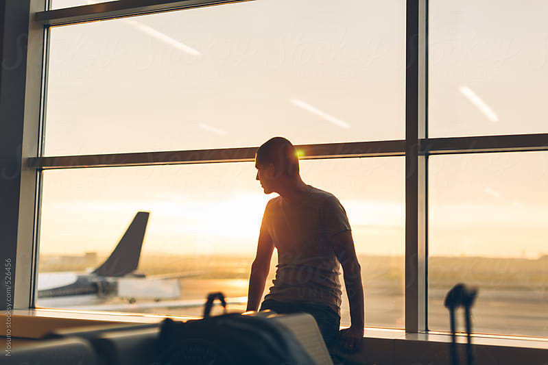 Man Sitting at the Airport Gate and Enjoying Sunrise by Mosuno for Stocksy United