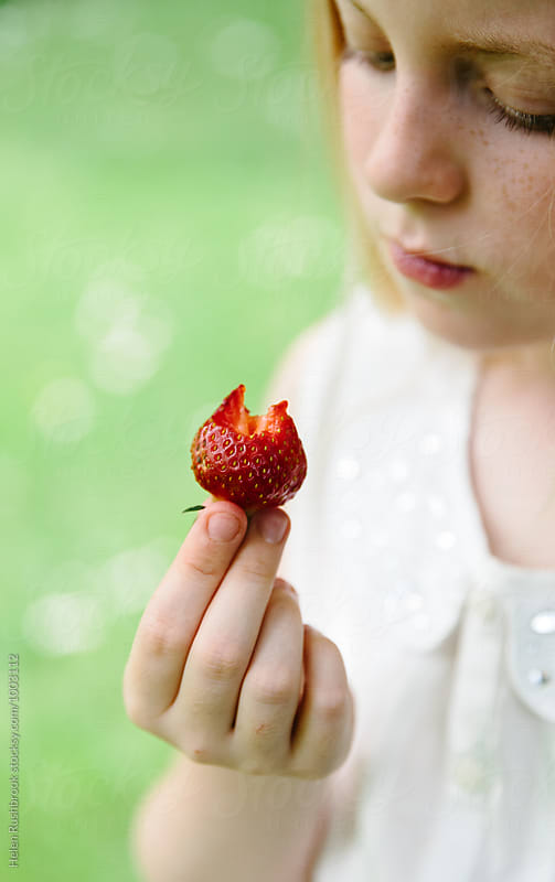 a little girl contemplating a half-eaten strawberry by Helen Rushbrook for Stocksy United