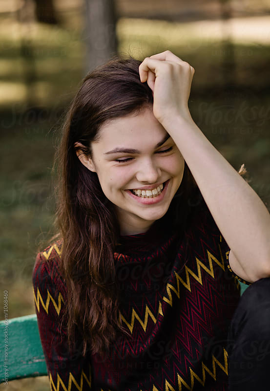 Pretty laughing woman on bench  by Sergey Filimonov for Stocksy United