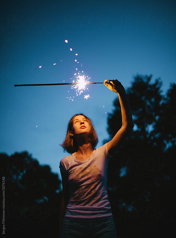 Portrait of young attractive celebrating woman holding sparkles by Sergey Filimonov for Stocksy United