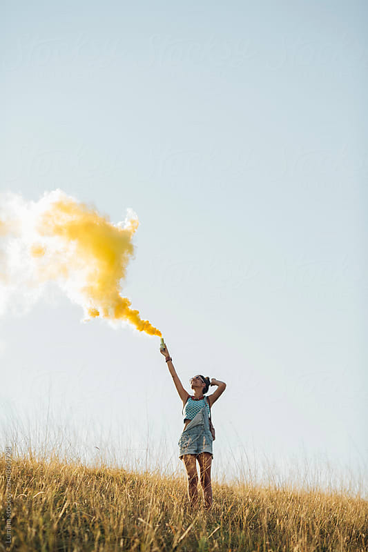Happy Girl Holding a Yellow Smoke Bomb by Lumina for Stocksy United