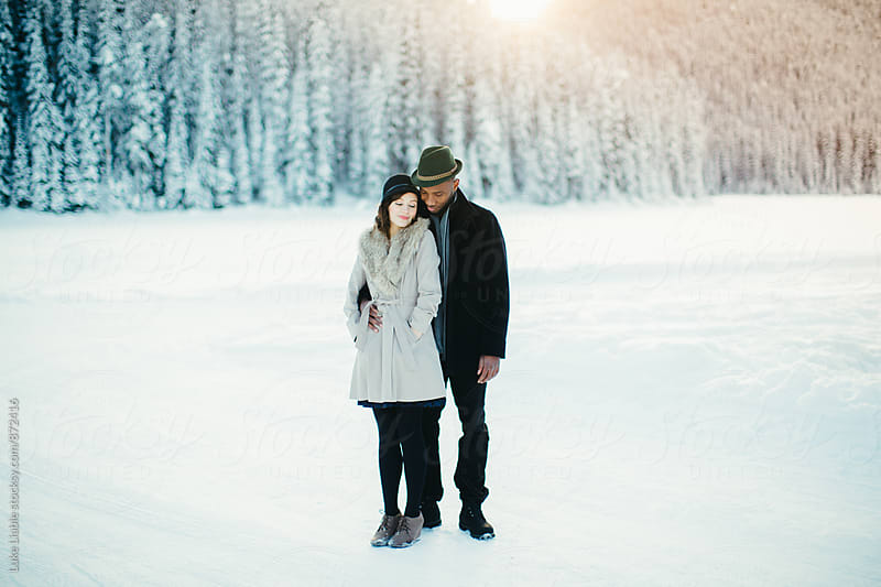 Young mixed race couple laughing in love on snow covered winter lake by Luke Liable for Stocksy United