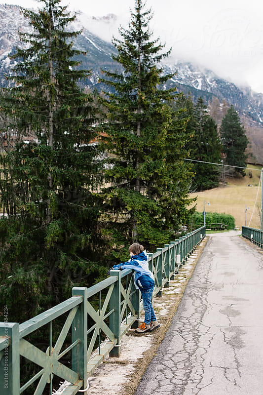 Boy watching the river from a mountain bridge by Beatrix Boros for Stocksy United