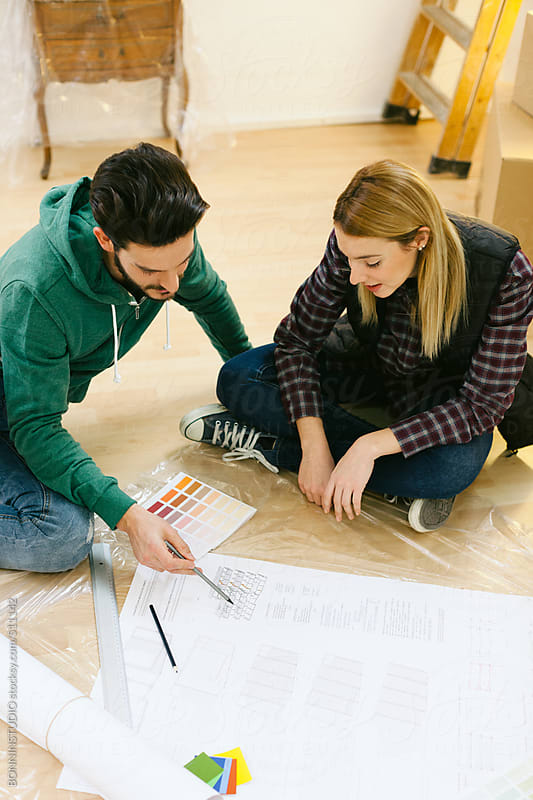 Young couple looking a furniture instructions for your new home.  by BONNINSTUDIO for Stocksy United