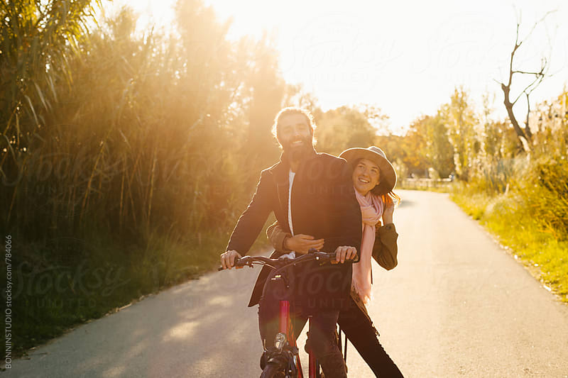 Couple riding a bicycle on a forest road. by BONNINSTUDIO for Stocksy United