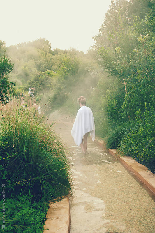 girl walking in a hot springs resort on a winter's morning by Gillian Vann for Stocksy United