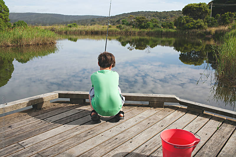 young boy fishing off pier / jetty in Australia by Natalie JEFFCOTT for Stocksy United