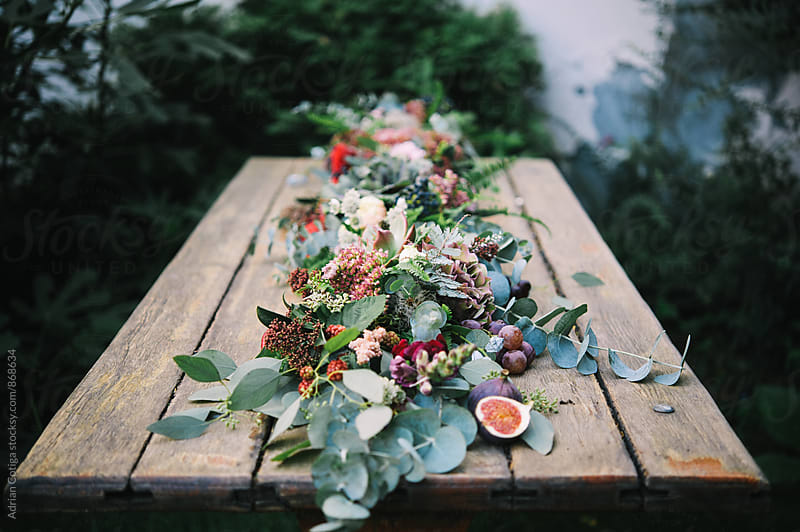 Amazing centerpiece for an autumn celebration with fruits, flowers and succulents by Adrian Cotiga for Stocksy United