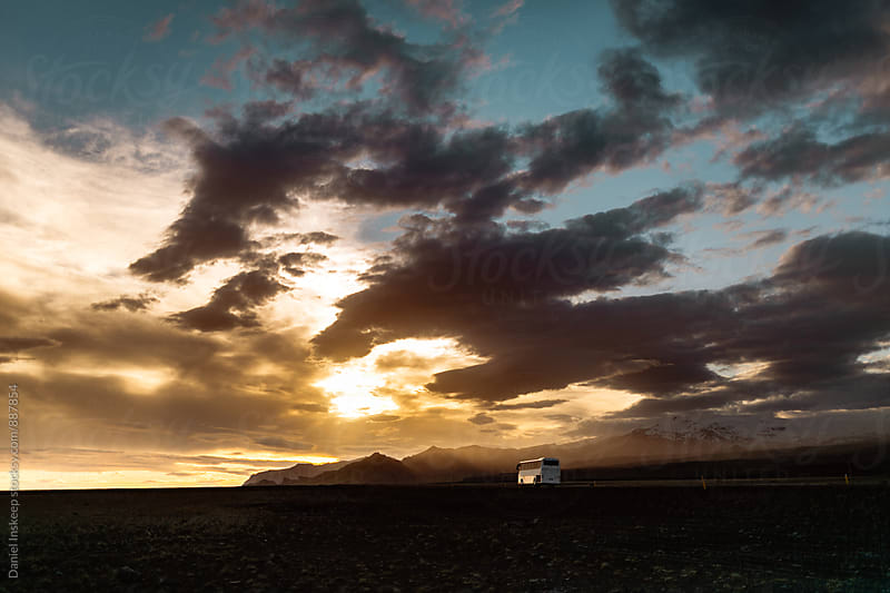 An Iceland Tour Bus Driving Off into the Sunset by Daniel Inskeep for Stocksy United