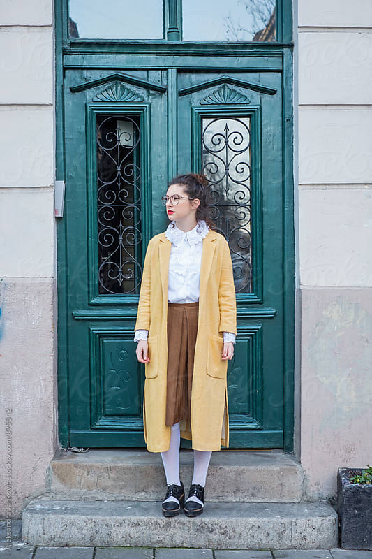 Stylish Woman in a Vintage Yellow Coat Standing in Front of the Green Doors by Aleksandra Jankovic for Stocksy United