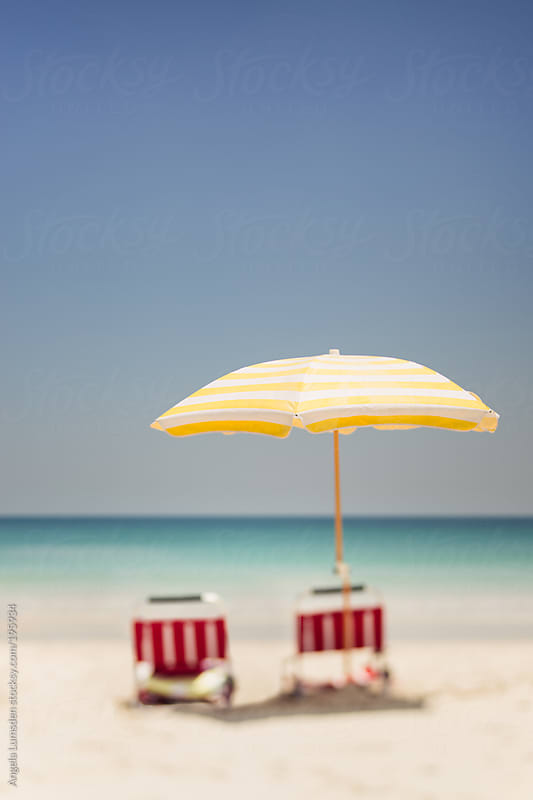Beach umbrella and chairs in the sand at the seaside by Angela Lumsden for Stocksy United