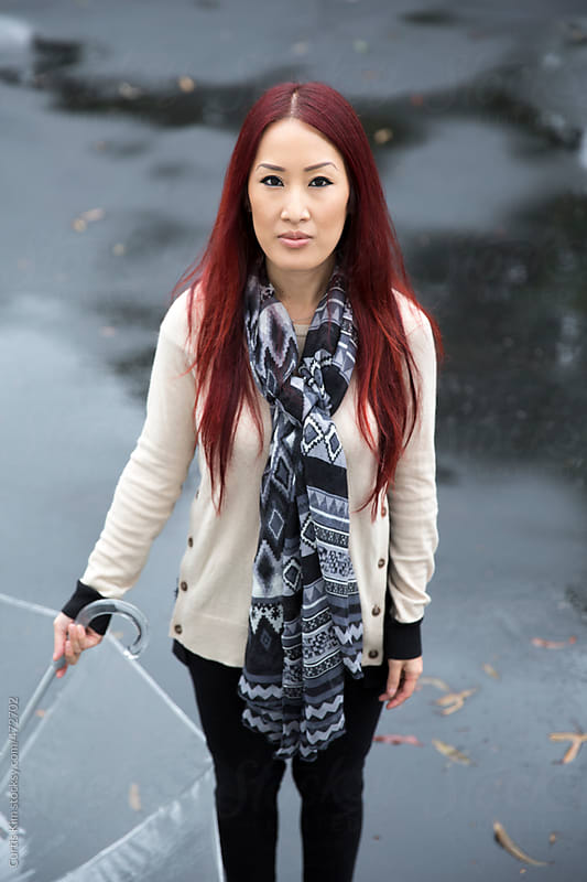 Woman with red hair holding an umbrella by Curtis Kim for Stocksy United