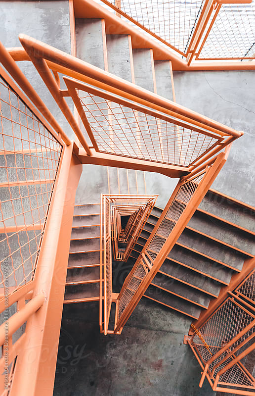 An orange moody stairwell taken from a top view  by Kristen Curette Hines for Stocksy United