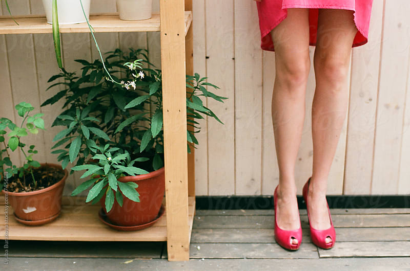 Woman's legs close to pots with plants by Lyuba Burakova for Stocksy United