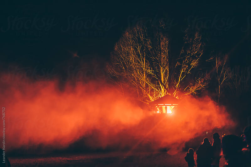 wooden tower with light illuminates a tree in red smoke by Leander Nardin for Stocksy United