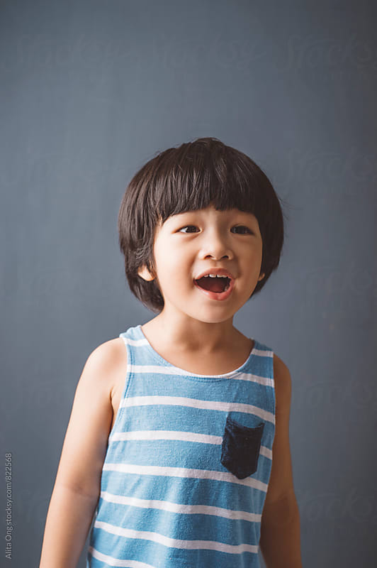 Portrait of a happy kid, singing by Alita Ong for Stocksy United