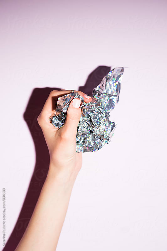 Female Hand Holding Shiny Silver Paper by Katarina Radovic for Stocksy United